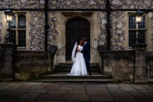 Bride and groom kiss on steps of Victoran Gothic flint-faced building lit by wrought-iron lamps
