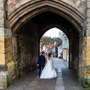 Bride and groom walk through the arch of Winchester's Westgate down towards the city centre