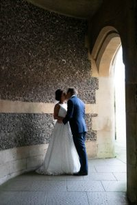 Bride and groom kiss beneath the arch of Winchester's Westgate