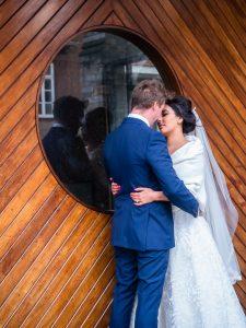 Bride holds groom around waist in front of wooden door with round window