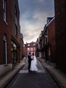 Dramtic portrait of bride and groom in city side street at sunset