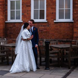 Groom kisses bride in front of red-brick building