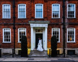 Groom kisses bride on steps of red-brick Victorian town-house, now the Hotel du Vin