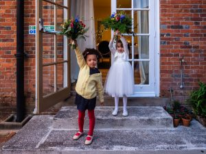 Two little girls, one in red tights and yellow cardigan and the other in white, hold aloft wedding bouquets on the steps outside french doors