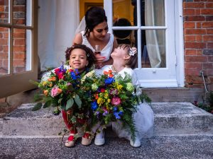 Bride sits on the steps with two little girls holding bouquets