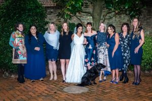 Group shot of bride and her friends with a seated black labrador