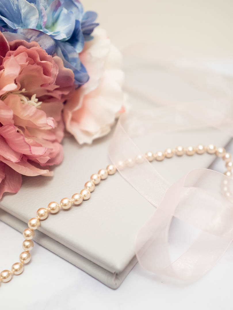 Pearls and peonies on a beige leather-bound wedding album from Dom Brenton Photography