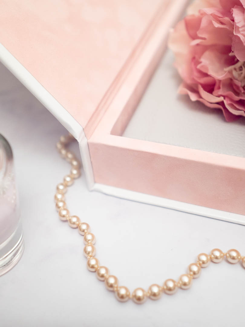 Pearls draped across the presentation box of a wedding album from Dom Brenton Photography