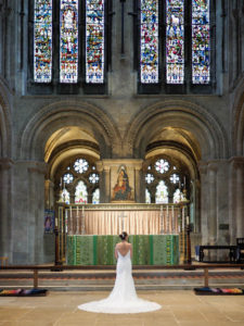 Bride in wedding dress beneath the east window in Romsey Abbey – Dom Brenton Photography