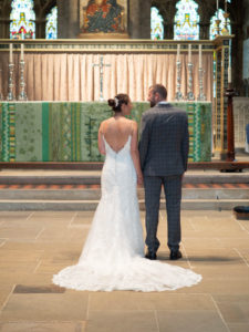 'Newlywed' couple in front of the high altar in Romsey Abbey – Dom Brenton Photography