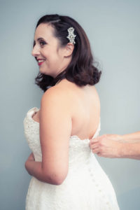 Smiling bride being buttoned into Nicola Anne Bridal wedding dress