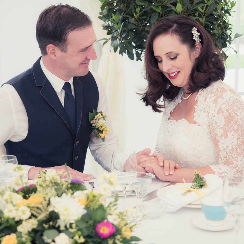 Bride and groom holding hands at their dining table in The Orangery Suite marquee
