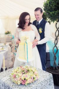 Bride and groom cutting a vintage yellow wedding cake in The Orangery Suite marquee