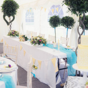 Vintage-styled top table and ornamental topiary in The Orangery Suite marquee