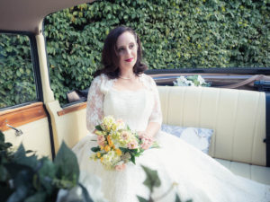 Bride holding bouquet in back of Regency Launaulette wedding car