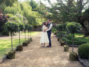 Groom holds his bride on a gravel path decorated with ornamental bay trees at The Orangery Suite