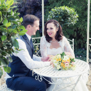 Bride and groom beneath pergola flanked by ornamental bay trees at The Orangery Suite