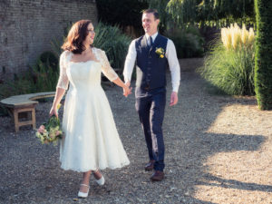 Smiling bride leads groom along gravel path in the grounds of The Orangery Suite