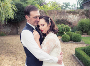 Bride and groom embrace in the grounds of The Orangery Suite