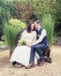 Bride and groom snuggled together on a bench in the grounds of The Orangery Suite