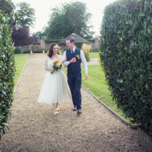 Bride and groom walk towards the camera in the grounds of The Orangery Suite