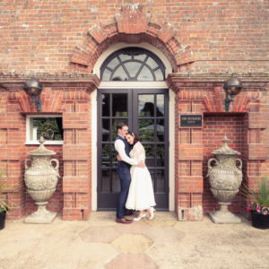 Bride and groom in front of the entrance to The Orangery Suite