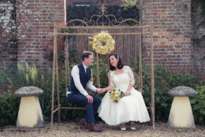 Bride and groom holding hands on a rustic swing in the grounds of The Orangery Suite