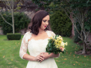Bride in a Nicola Anne Bridal dress admiring her bouquet in the grounds of The Orangery Suite