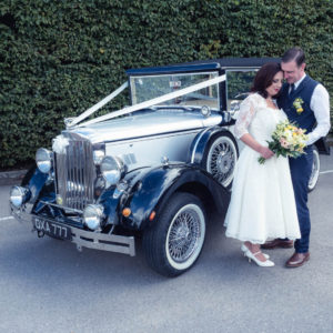 Bride and groom holding bouquet in front of  Regency Laundaulette vintage wedding car