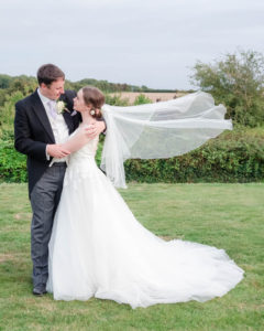 Bride with billowing veil embraces groom