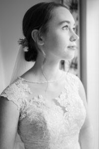 Classic monochrome window-lit image of Michaela in her wedding dress
