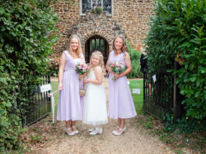 Bridesmaids pose by the gates outside Alderholt church