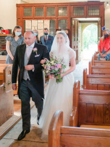 Michaela walks up the aisle in church on her father's arm