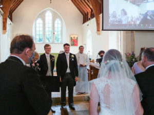 Rupert smiles at Michaela as she walks up the aisle to join him in church
