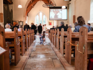 Little bridesmaids being taken to a pew after leading the entrance of the bride