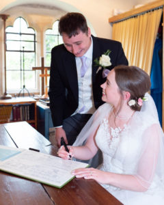 Michaela, seated in front of the marriage register, looks at Rupert as he gazes down at her signature