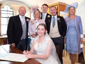 Michaela looks up from the marriage register as Rupert and both sets of parents pose for the camera