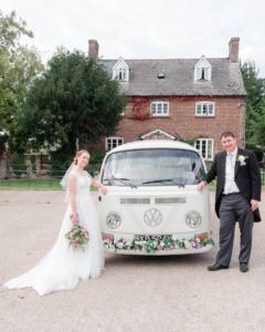 Michaela and Rupert pose on either side of Lillie, the VW camper van from Dorset Dubhire in which they travelled to their wedding reception