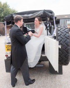 Rupert helps Michaela into the back of his Land Rover