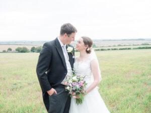 Michaela and Rupert gaze adoringly at each other in a field