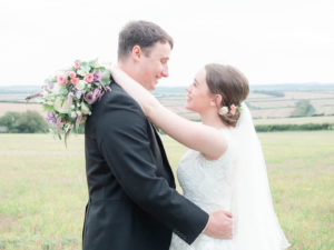 Michaela and Rupert embrace with her bridal bouquet behind his neck
