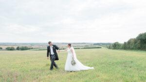 Rupert leads Michaela across a field
