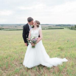 Michaela and Rupert kiss in a field