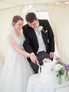 Michaela and Rupert cut their wedding cake in a marquee
