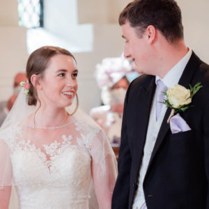 Michaela and Rupert gaze lovingly at each other during their wedding service