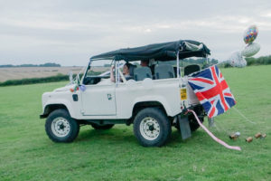 Michaela and Rupert leave their wedding reception in a white Land Rover, trailing balloons and tin cans behind them
