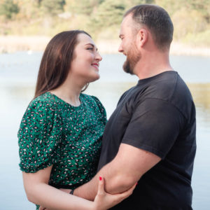 Couple on engagement photo session, gazing lovingly at each other by the lake on Ham Common, Poole Harbour, Dorset