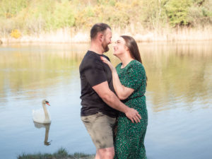 Couple on engagement photo session, embracing as a swan looks on by the lake on Ham Common, Poole Harbour, Dorset