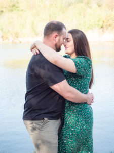 Couple on engagement photo session, embracing by the lake on Ham Common, Poole Harbour, Dorset