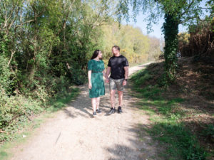 Couple on engagement photo session, walking hand-in-hand along a path on Ham Common, Poole Harbour, Dorset